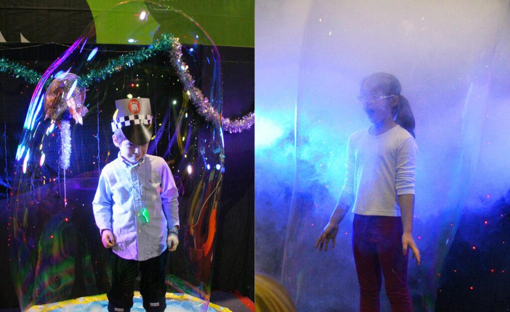Niños dentro de enormes burbujas de jabón